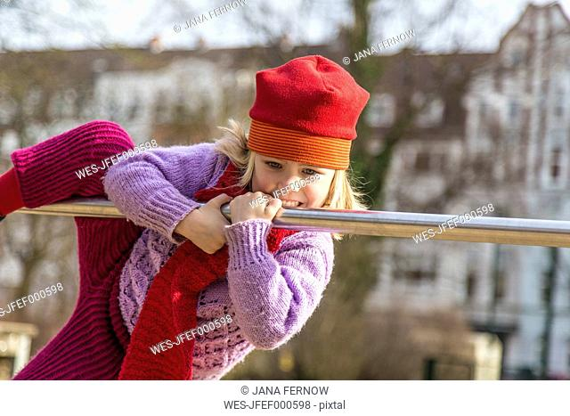 Germany, Kiel, Little girl with red cap playing on bar