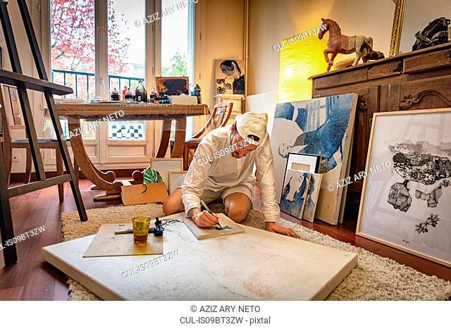 Artist working on canvas in studio