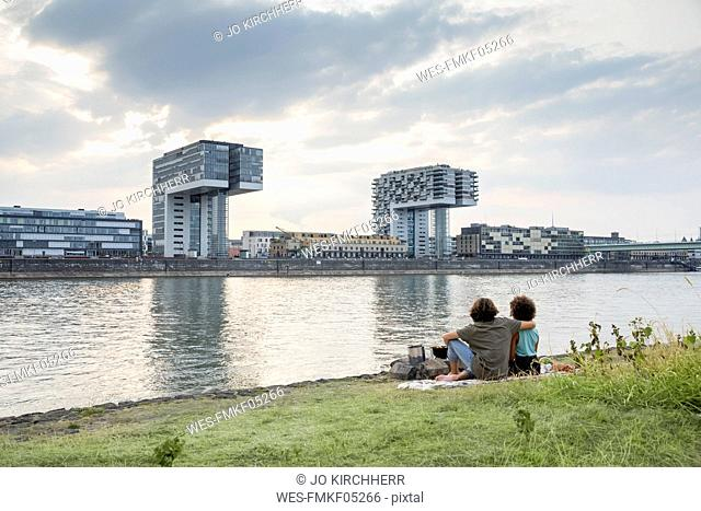 Germany, Cologne, couple relaxing at the riverside at sunset