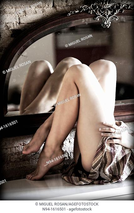 Bent legs of a young woman lying down and reflected in a mirror