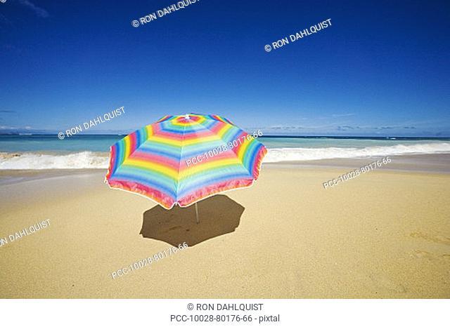 Brightly colored beach umbrella on the sand near the ocean