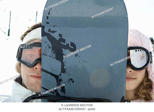 Two young friends peeking at camera from behind snowboard, portrait
