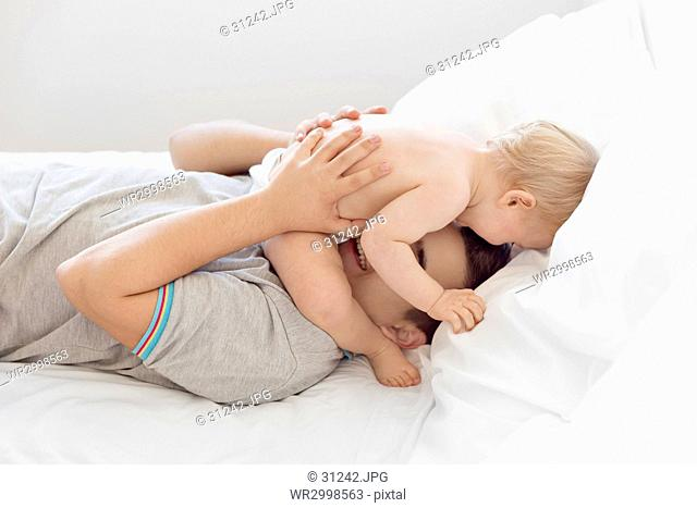 Teenage boy lying on his back on a bed, playing with baby boy