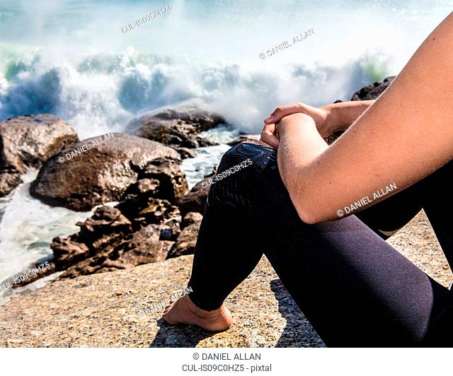 Young female surfer sitting on beach rock amongst ocean waves, cropped, Cape Town, Western Cape, South Africa