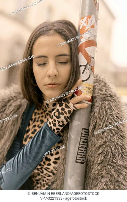 portrait of sensitive woman with closed eyes leaning on lamppost at street in city, exhausted mood, tired, sleepy, Munich, Germany