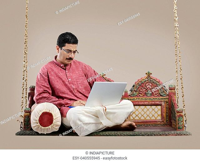 South Indian man working on a laptop
