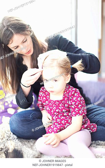 Mother making daughters hair in morning