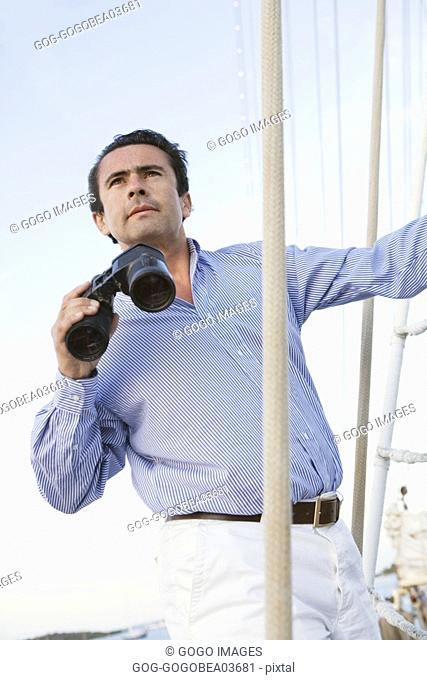 Man using binoculars on ship deck