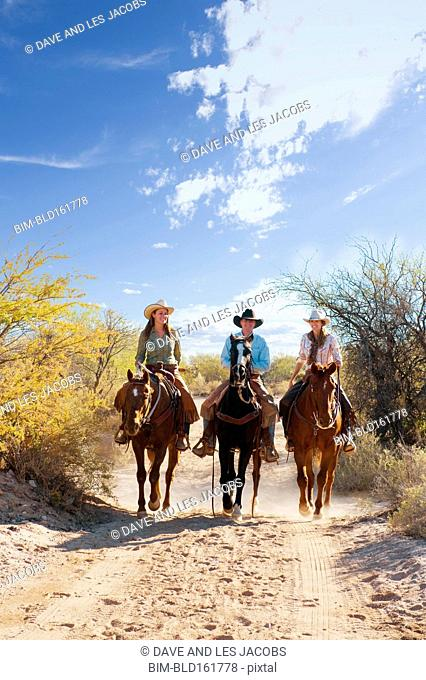 Caucasian ranchers riding horse on dirt path