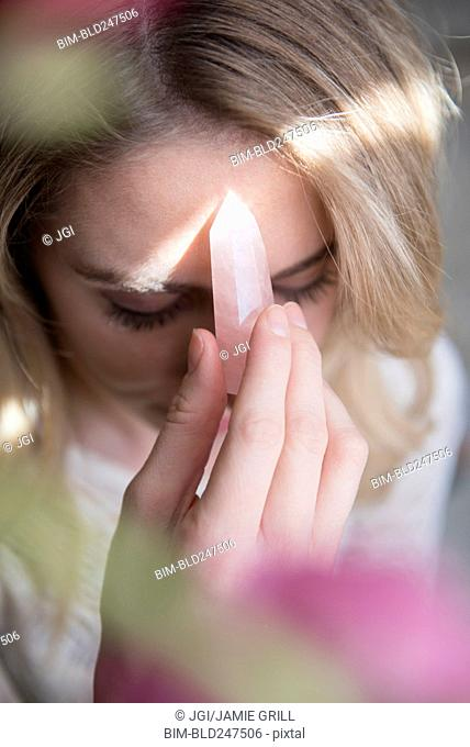 Caucasian woman holding crystal to forehead