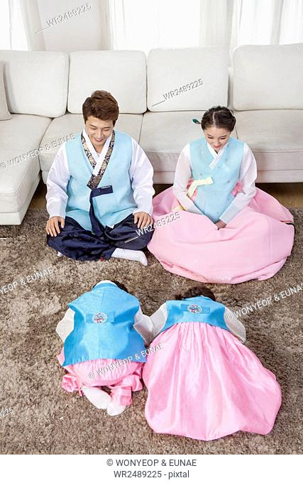 Korean son and daughter sitting and bowing to their parents on traditional Korean holiday
