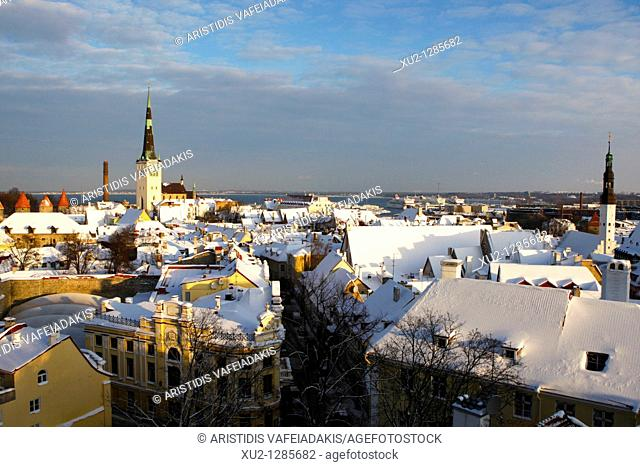 Snowy roofs in Talin's old town with the port in the background  Christmas in Tallin Estonia