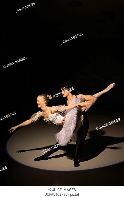 Male and female ballet dancers dancing on stage in the spotlight