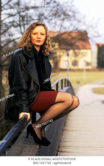 Well-dressed woman sitting on railing at a footbridge and looks in the camera - Bavaria/Germany