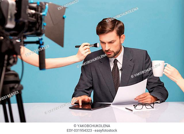 Attractive young tv newscaster is preparing for report. He is sitting at the desk and using a tablet with interest. The female hand is doing him make-up while...