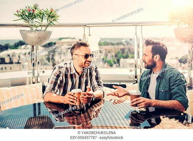 Interesting meeting. Male friends sitting at the table and communicating. They looking at each other and holding cups of coffee