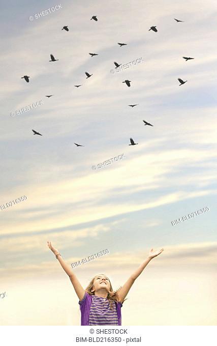 Caucasian girl cheering under flock of birds