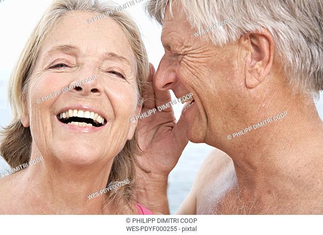 Spain, Senior man whispering into ear of woman, smiling