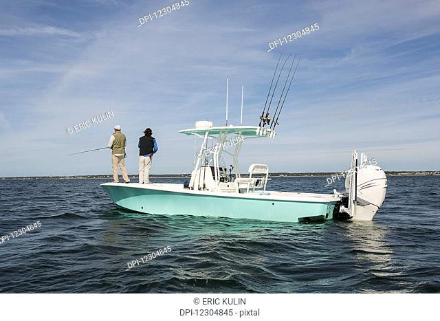 Men standing on the end of a fishing boat and fishing in the Atlantic Ocean off the coast of Cape Cod; Massachusetts, United States of America