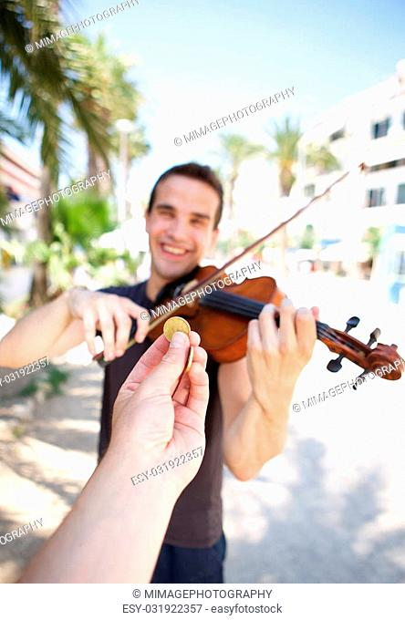 Hand paying money to busker man playing violin outside