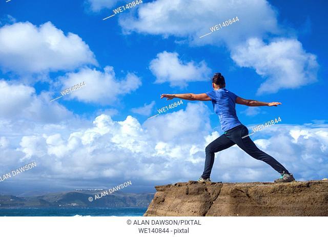 Mature female jogger warming up with Yoga stretching exercises at El Confital beach, Las Palmas, Gran Canaria, Canary Islands, Spain