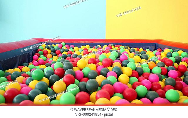 Cute little boy emerging from ball pool on blue and yellow background