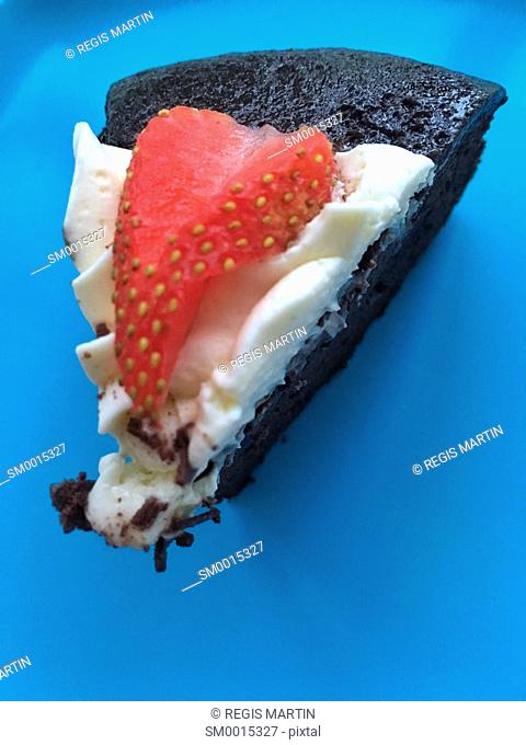Slice of cake with a cute strawberry on top, view from above on a blue plate