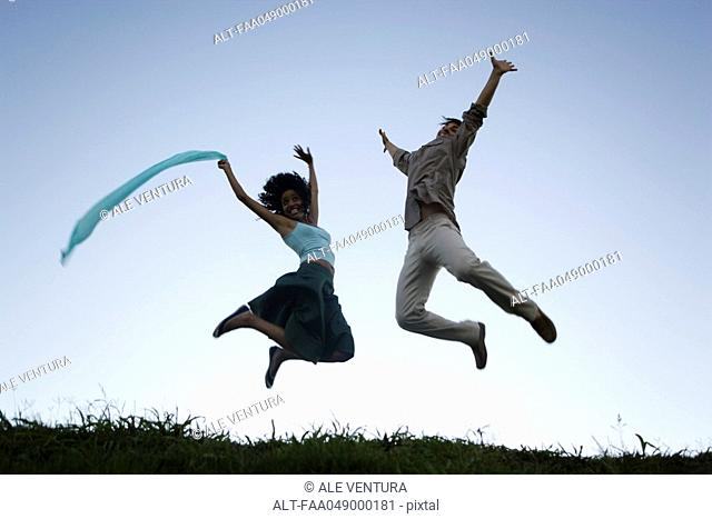 Young couple exuberantly jumping with arms raised wearing expressions of joy