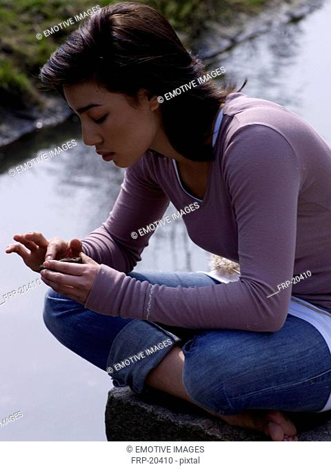 Relaxed dark-haired woman at pond
