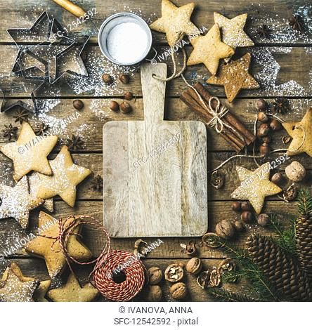 Gingerbread cookies, sugar powder, nuts, spices, baking molds, fir-tree branch, pine cones on rustic background