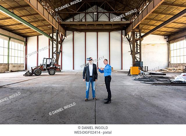 Two businessmen with VR glasses talking in old industrial hall