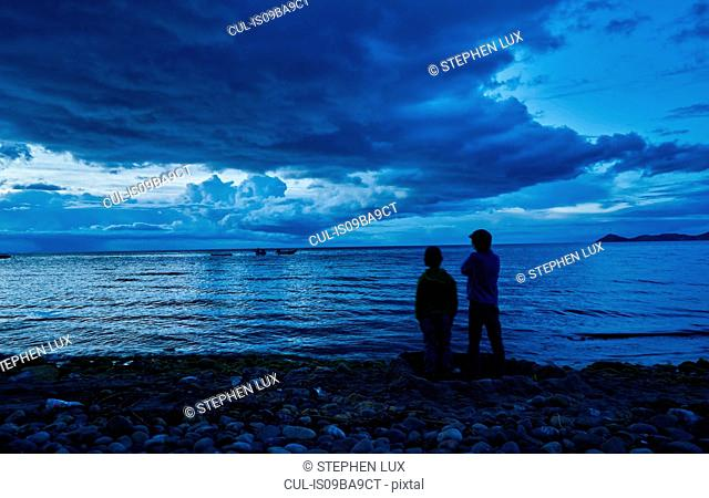 Two boys standing beside lake, looking at view, rear view, Copacabana, Oruro, Bolivia, South America