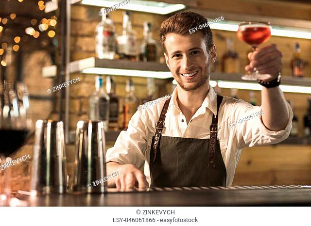 There you go. Pleasant young barman standing behind the bar counter and handing a cocktail to the customer while smiling