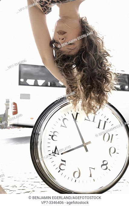 young woman upside down with clock at street in front of bus, public transportation
