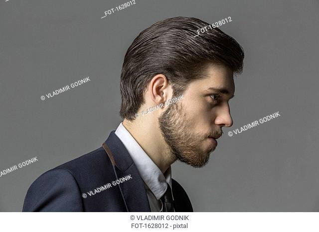 Side view of thoughtful businessman against gray background