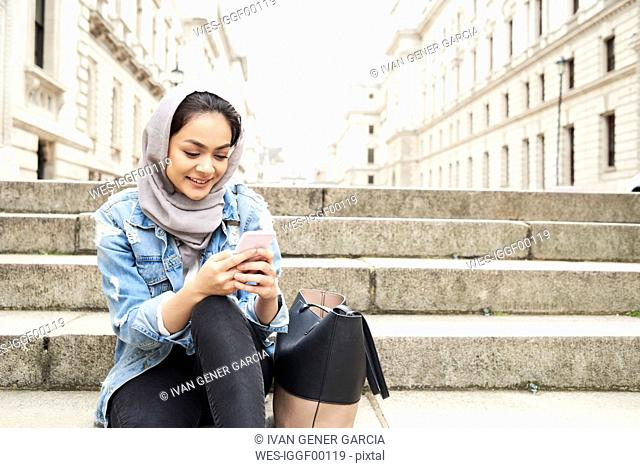 UK, England, London, young woman wearing hijab using cell phone in the city