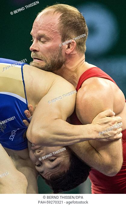 Germany's Marcel Ewald (red) competes with Viktor Lebedev (blue) of Russia in the wrestling Men's 57kg Freestyle Final at the Baku 2015 European Games in the...