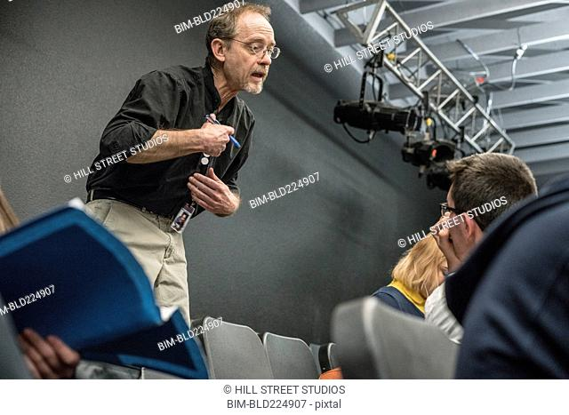 Caucasian teacher gesturing to student in high school drama class