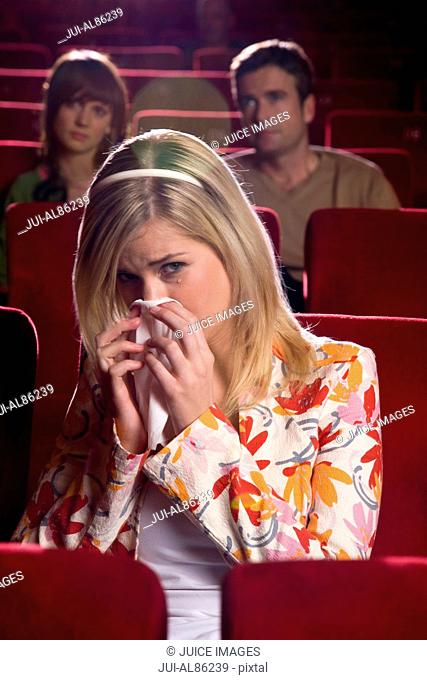 Woman blowing nose in movie theater