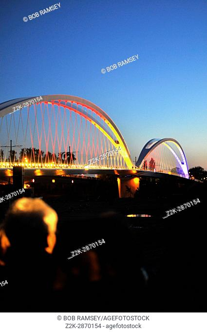 Illumination lights on the metallic bridge between the city of Strasbourg in France and the city of Kehl in Germany, with people life