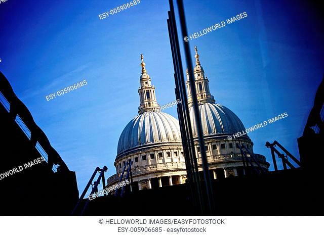 St Paul's Cathedral dome against deep blue sky reflected in glass of modern building, London, England, Europe