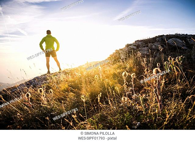 Italy, mountain running man standing on trail looking at sunset