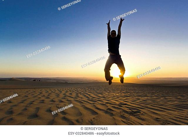 jumping man with hands up at sunset in desert with shining sun