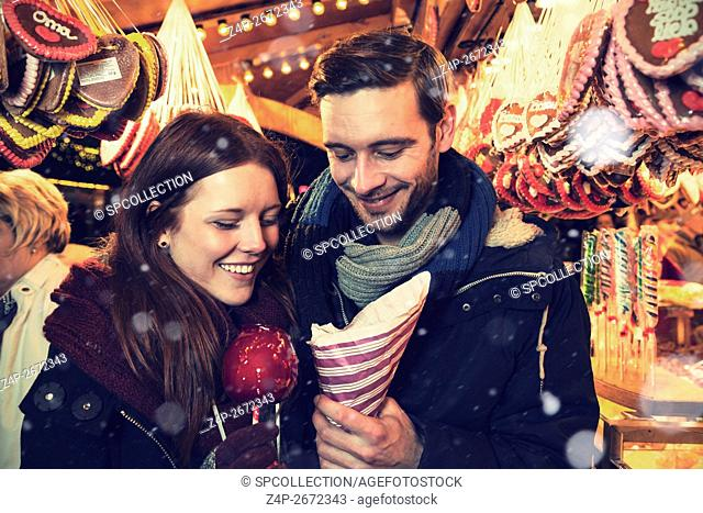 Couple with candy on christmas market