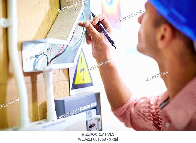 Electrician looking at wire at distribution board