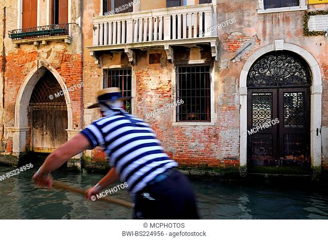 Venetian gondolier rowing along a canal, Italy, Venice