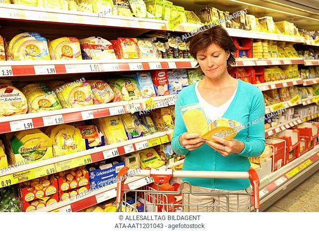 Woman choosing cheese in the supermarket