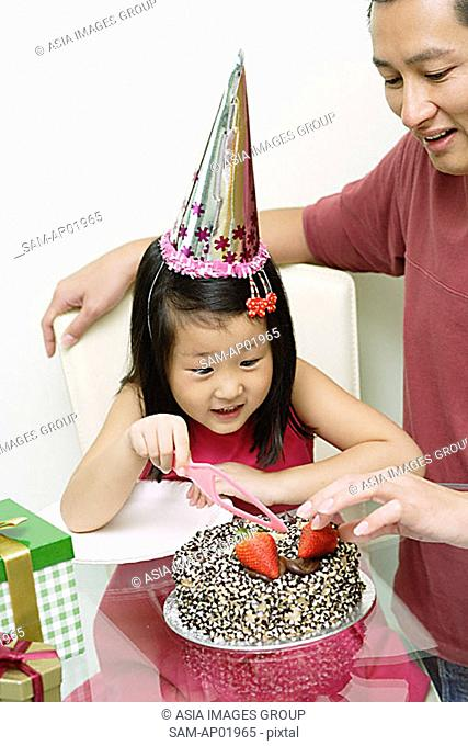 Father and daughter in front of birthday cake, daughter holding cake knife