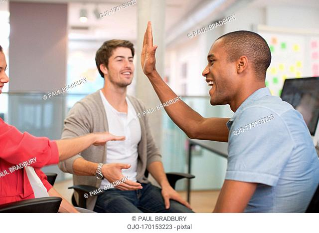 Business people high fiving in meeting
