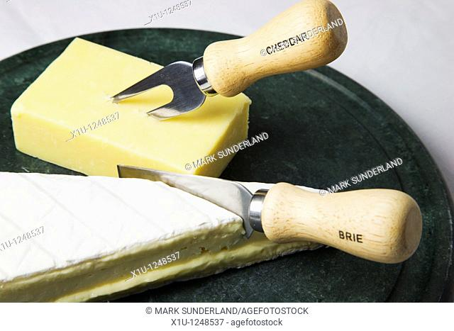 Brie and Cheddar on a Cheese Board with Brie Knife and Cheddar Fork